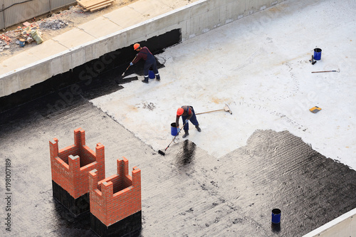 Fotografering Two workers conduct waterproofing of the roof with bitumen