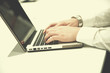 hands typing on laptop at meeting