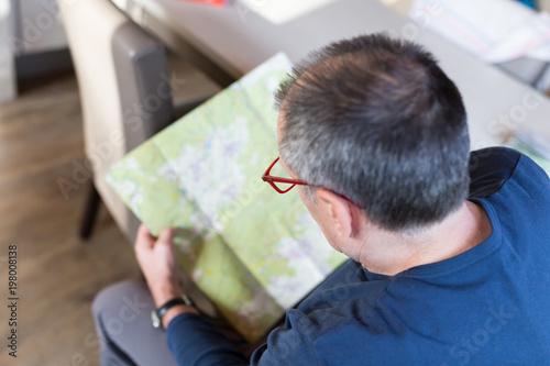 Senior man planning trip using a map
