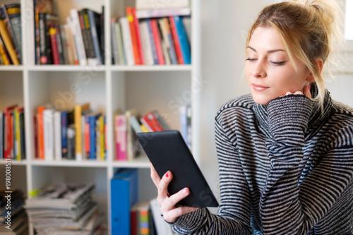 Young girl reading e-book reader next to colorful bookshelf Tapéta, Fotótapéta