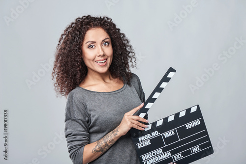 Excited curly female holding movie clapper board, slate film. Wallpaper Mural