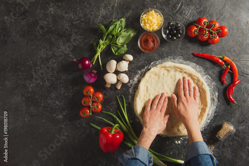 Fotografie, Obraz  cropped shot of woman cooking italian pizza with fresh ingredients on dark table