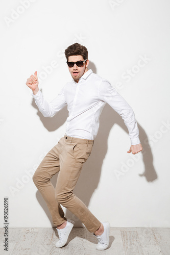 Photo Full length photo of positive guy in shirt and trousers dancing in black sunglas