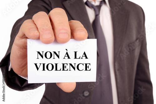 Photo Homme tenant une carte sur laquelle est écrit non à la violence