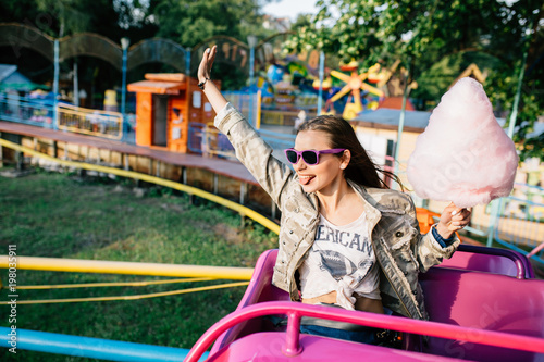 Fotografía  Excited girl with cotton candy riding a children's roller coaster