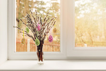 Easter Decoration - Vase With Colorful Eggs Hanging In Pussy Willow Branches On Window Sill