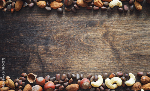 Different nuts on a wooden table. Cedar, cashew, hazelnut, walnu