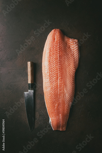 Whole raw uncooked salmon fillet with chef's knife over dark brown texture background Poster Mural XXL