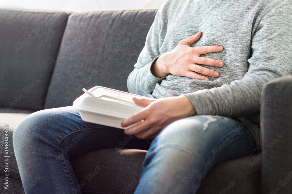 Fototapety, obrazy: Stomach pain, food poisoning or digestion problem after fast junk food. Man ate too much and is holding belly with hand. Indigestion, heart burn or unhealthy diet.