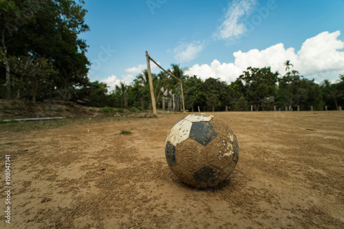 Fotografija  close up old football on ground at a dirt pitch