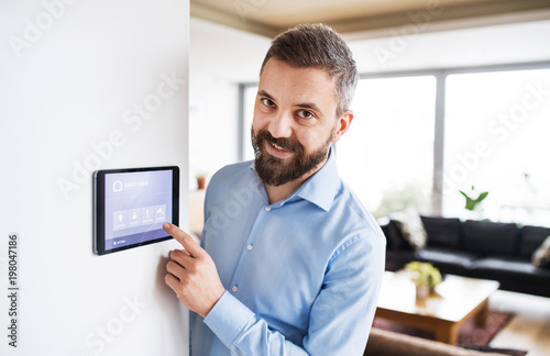 Fotografía A man pointing to a tablet with smart home screen.