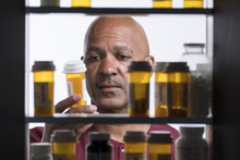 Man Taking Bottle Of Pills  From Medicine Cabinet