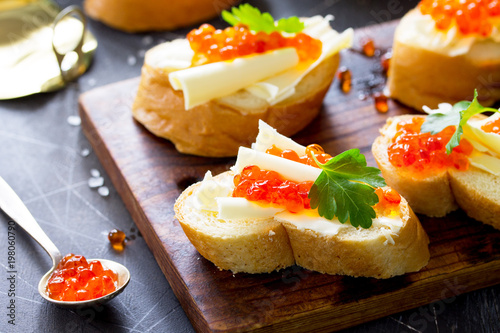 Spoed Fotobehang Voorgerecht Festive snack. Sandwiches with red caviar, isolated on dark concrete background.