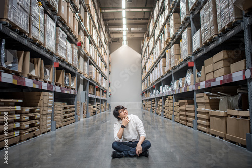 Young Asian man sitting between paper box shelves in warehouse choosing what to Canvas Print
