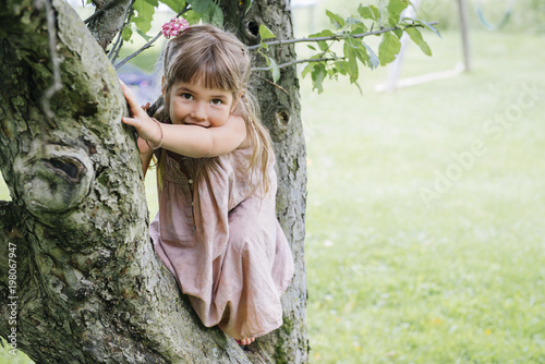 Portrait of cute playful girl sitting on tree against grassy field at park