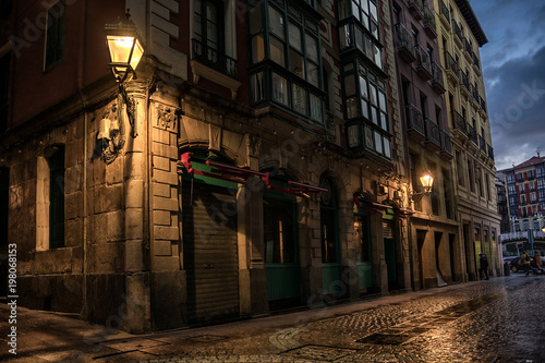 Canvas-taulu Narrow street corner with warm old lamp in the old city in Bilbao