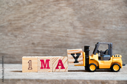 Fényképezés  Toy forklift hold block Y to complete word 1may on wood background (Concept for