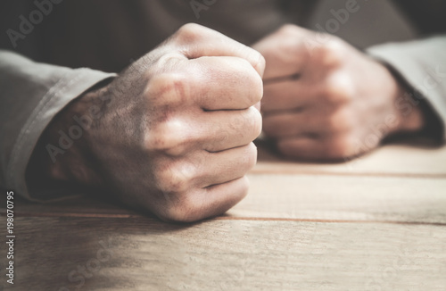 Fotografia Angry man fists in the table.