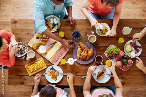Fotografia food, eating and family concept - group of people having breakfast and sitting a