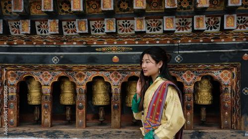 Fotografía  Bhutanese young woman wearing a kira (national dress) standing in front of praye