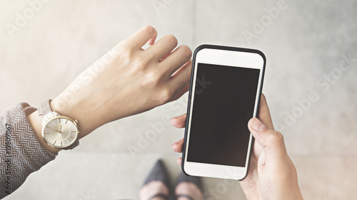 Woman looking her watch and holding mobile phone