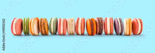 Poster Macarons French macarons large group lined up on light blue background