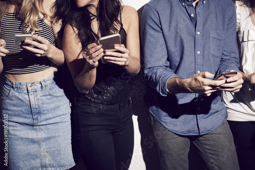 Midsection of male and female friends texting on smart phones