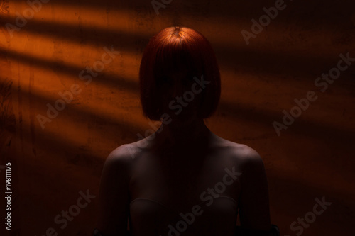 Fotografía  silhouette of a mysterious red-haired woman with bare shoulders, portrait of an