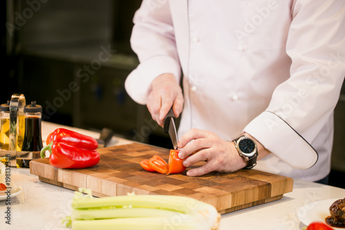 Fototapety, obrazy: closeup cropped photo of man with black watch cutting tomato on a cutting board in the kitchen. well-balanced food