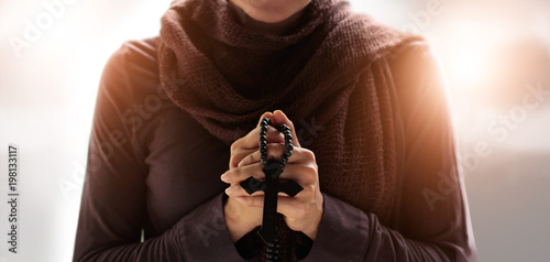 Canvas Print - Christian Religion concept. Woman hands praying with rosary and wooden cross on soft background.