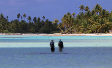 Fly-fisherman And Guide Walking On Flats In Turquoise Waters In French Polynesia