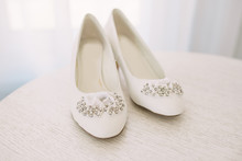 Elegant Women's Wedding Shoes With Rhinestones On A Light Background, The Fees Of The Bride, Selective Focus