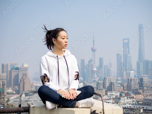 Beautiful young brunette woman sit on top of mansion roof with blur Shanghai Bund landmark buildings background Poster