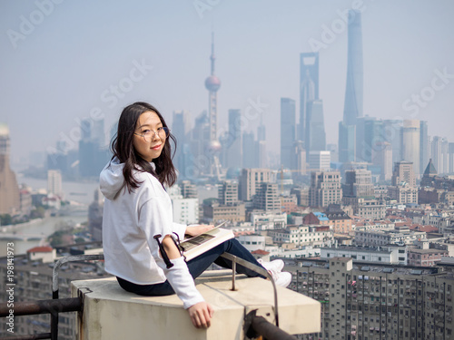 Photo  Beautiful young brunette woman sit on top of mansion roof with blur Shanghai Bund landmark buildings background