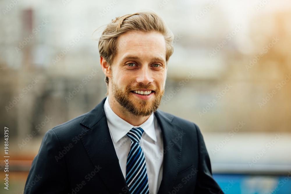 Fototapeta elegant blonde man in suit outside using his cellphone