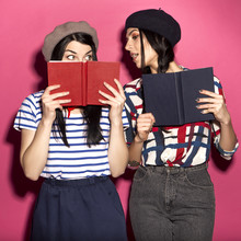 Two Caucasian Brunette Hipster Woman In Casual Stylish French Outfit With Beret, Having Fun Reading And Peaking In Each Other Books. They Standing On A Bright Pink Background. Cheerful, Happy Emotions