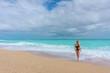 beautiful blonde girl in a black bathing suit walking on an empty Caribbean beach