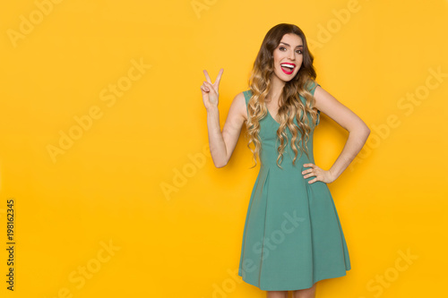 Laughing Woman In Green Mini Dress Is Showing Peace Hand Sign Poster