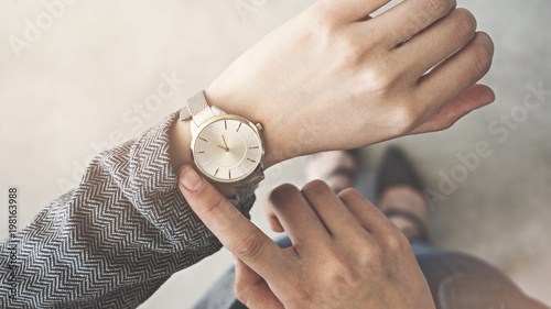 Woman looking her watch stand up