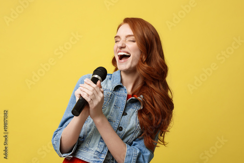 Lifestyle and People Concept: Expressive girl singing with a microphone, isolated bright yellow background. - 198171382