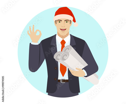 Businessman in Santa hat holding the project plans and showing a okay hand sign Canvas Print