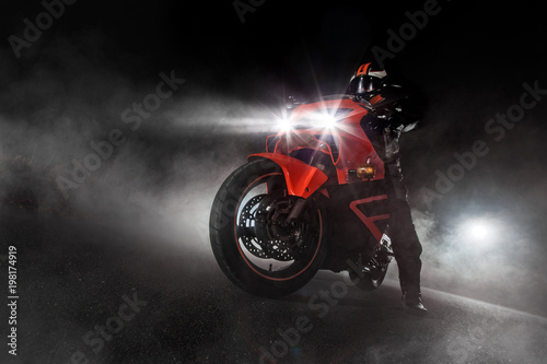 Fotografiet  Supersport motorcycle driver at night with smoke around