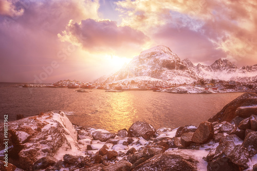 Tuinposter Zalm Scenery winter landscape in the Norway. Dramatic color sunset sky over the mountains and sea. Panoramic view of small cozy northern village Å, O on the edge of the Lofoten Islands