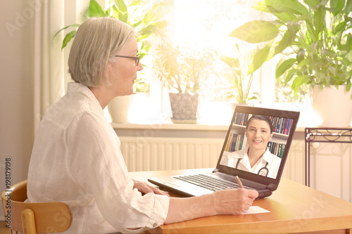 Senior woman in her sunny living room in front of a laptop making notes during a Fototapeta
