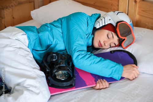 Tuinposter Ontspanning Woman in sports clothes with snowboard sleeping on bed. Winter vacation