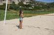 Little cute girl holding in her hands volleyball net. Beach volleyball in the summer