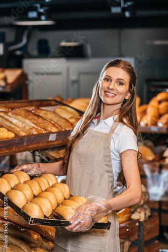 Cuadros en Lienzo smiling shop assistant arranging loafs of bread in shopping market