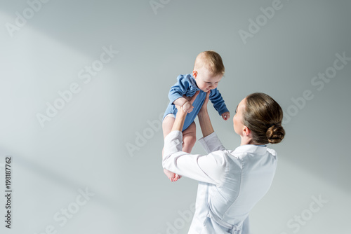 Fotografiet  rear view of female pediatrician playing with little baby on grey