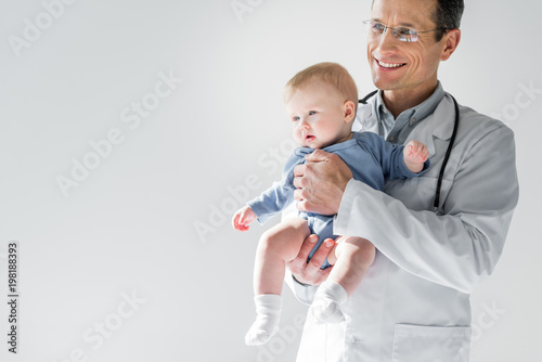Carta da parati handsome adult pediatrician holding little baby isolated on grey