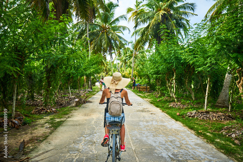 Fotomural woman on a bicycle crosses vanilla plantations, dique island, se